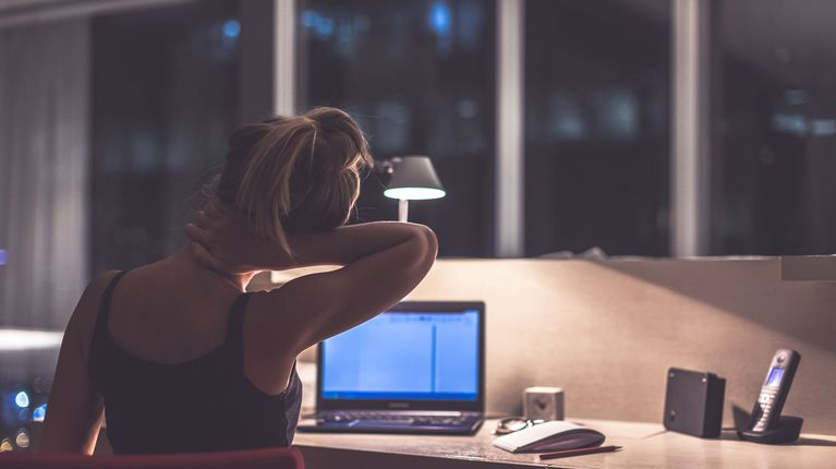 Woman stretching in front of computer screen at night