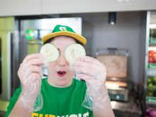 Subway Sandwich Artist holding cucumber slices over her eyes