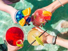 Four hands hold cocktails at a pool